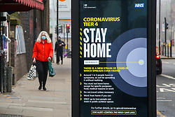 © Licensed to London News Pictures. 28/12/2020. London, UK. A woman wearing a face covering in north London walks past the government's 'Coronavirus Tier 4 - Stay Home'' publicity campaign poster. A new COVID-19 mutation has been discovered in the UK and many parts of the country came under Tier 4 restrictions on Boxing Day. The Medicines and Healthcare Products Regulatory Agency (MHRA) is likely to approve a COVID-19 vaccine developed by Oxford University and AstraZeneca this week. Photo credit: Dinendra Haria/LNP