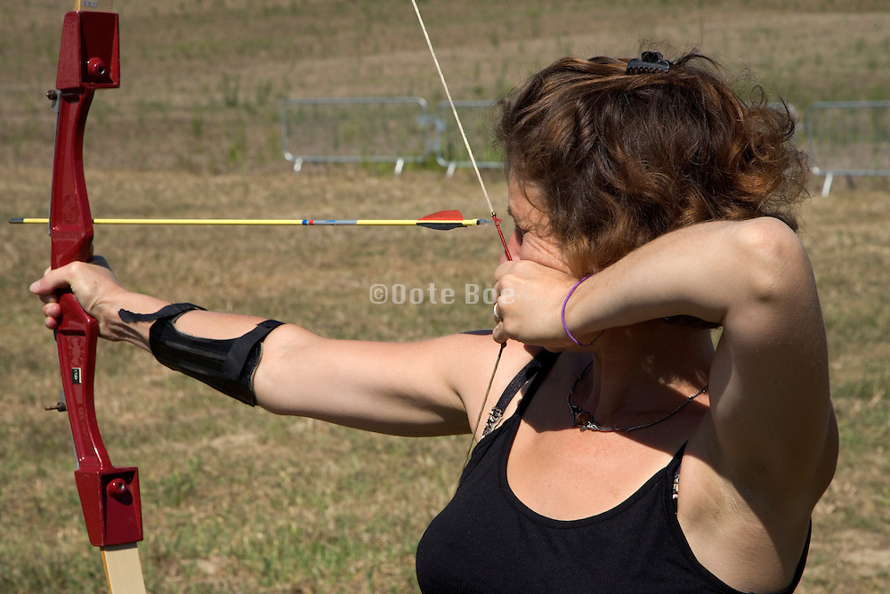 young woman aiming her bow and arrow