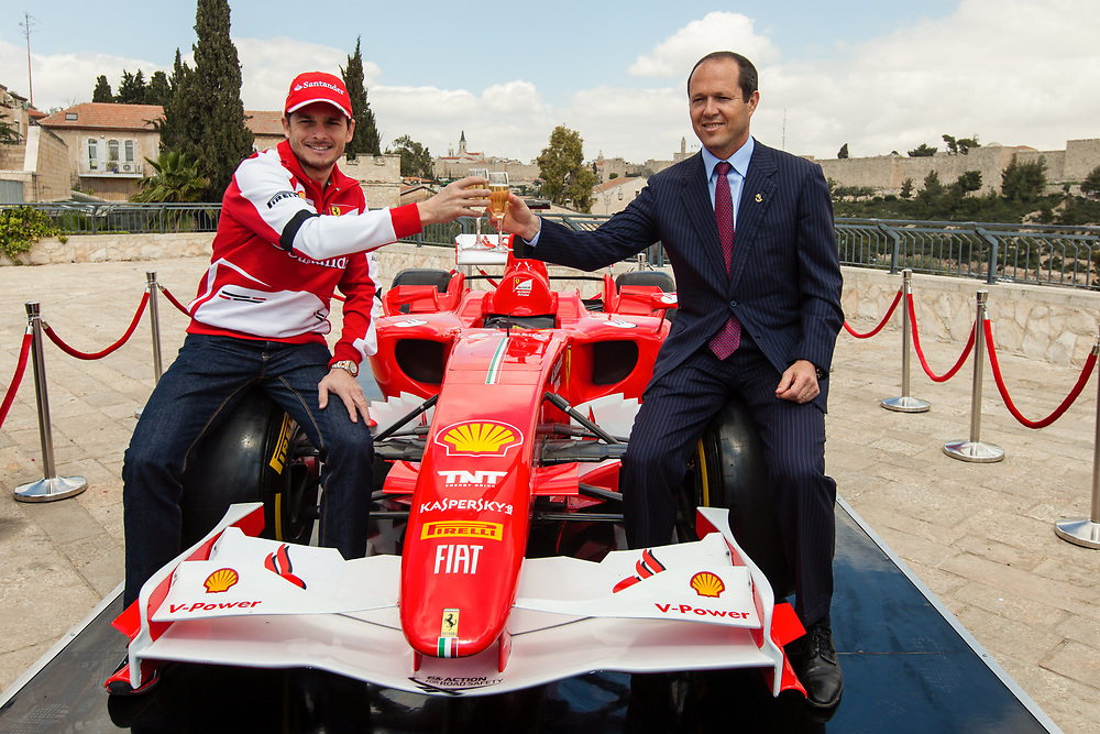 Formula One Scuderia Ferrari team driver Giancarlo Fisichella (L) and Mayor of Jerusalem Nir Barkat toast as they participate in a launch event ahead of 'Jerusalem Formula The Peace Road Show' in front of Jerusalem's old city walls, Israel, on March 18, 2013. The Formula One race in Jerusalem will take place on June 13-14 of 2013.