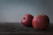 A rustic still life image of two Gala apples on wood with a subtle blue background. Rustic yet simplistic and a lovely addition to any kitchen or dining area