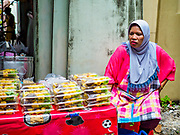 25 JUNE 2017 - BANGKOK, THAILAND: A Muslim snack vendor waits for customers in front of Ton Son Mosque before Eid al-Fitr services. Eid al-Fitr is also called Feast of Breaking the Fast, the Sugar Feast, Bayram (Bajram), the Sweet Festival or Hari Raya Puasa and the Lesser Eid. It is an important Muslim religious holiday that marks the end of Ramadan, the Islamic holy month of fasting. Muslims are not allowed to fast on Eid. The holiday celebrates the conclusion of the 29 or 30 days of dawn-to-sunset fasting Muslims do during the month of Ramadan. Islam is the second largest religion in Thailand. Government sources say about 5% of Thais are Muslim, many in the Muslim community say the number is closer to 10%.    PHOTO BY JACK KURTZ