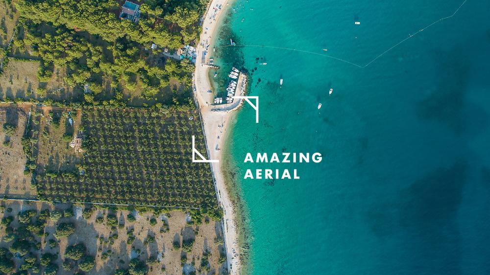 Aerial view of a small beach along the coastline near Gajac township, view of a few boats sailing along the shoreline, Lika-Senj, Croatia.