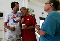 August 27, 2017 - Port Aransas, Texas, U.S. - ROBERT RAMSEY (left) consoles MELANIE ZURAWSKI who broke into tears as they gather with KATHY NIEHART at the emergency operations center in Port Aransas, seeking answers and aid in the aftermath of Hurricane Harvey. The trio was amongst a group of residents to stayed and rode out the category four storm instead of evacuating. All three of their homes were destroyed in the storm. (Credit Image: © Kin Man Hui/San Antonio Express-News via ZUMA Wire)