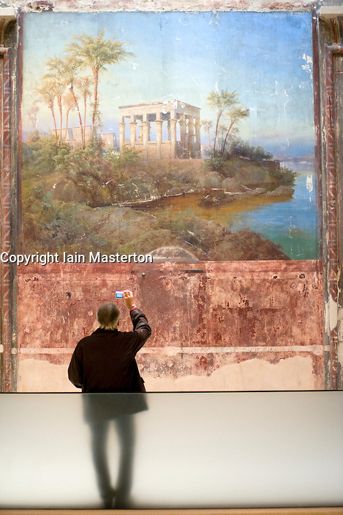 Visitors looking at old murals on wall in Egyptian courtyard gallery of newly renovated and reopened Neues Museum in Berlin 2009 Architectect David Chipperfield