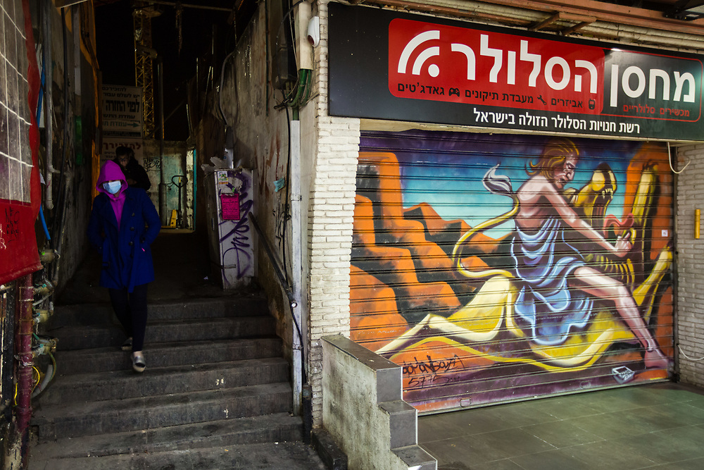 Israelis pass next to a graffiti depicting Samson killing a lion with his bare hands which was painted over a closed shutter at the Mahane Yehuda Market, often called 'The Shuk' in Jerusalem, Israel, on February 24, 2016.