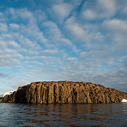 Cloud formations pass over a large rock monolith. Svalbard, Norway