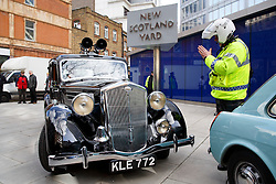 © licensed to London News Pictures. London, UK 26/02/2014. A veteran police car 1948 Wolseley parking outside New Scotland Yard as the Met's iconic cop cars dating back to 1948 taking part at a convoy through central London. Vehicles including the 1948 Wolseley, 1970 Morris, Minor 1000 and the 1973 Special Branch Rover P6 leaving Hampton Traffic Garage for the final time to head up to the Met's Peel Centre in Hendon which will be the new home of the fleet. Photo credit: Tolga Akmen/LNP
