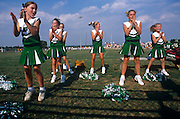 Young cheerleaders jump off the ground together during a Saturday morning High School football match in Mount Joy, Pennsylvania.