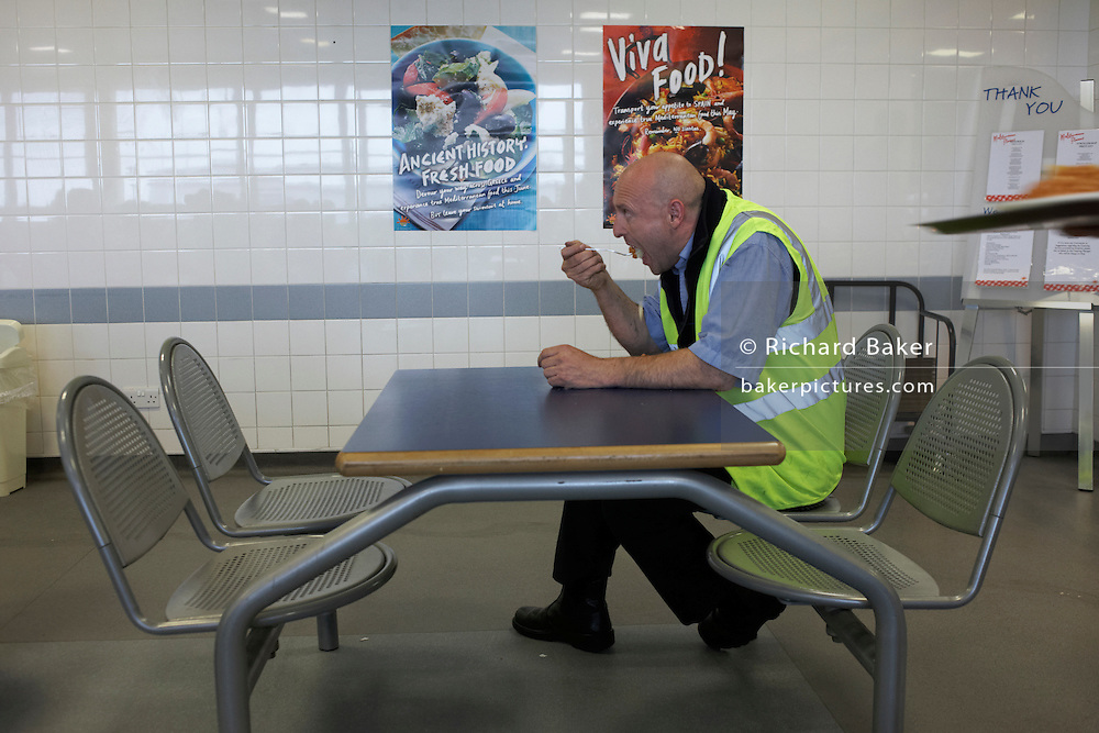 An employee of supermarket chain J Sainsbury's eats his lunch in the canteen of the company's Waltham Point logistics depot