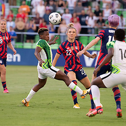 KRISTIE MEWIS (22) of Team USA threads between two Nigerian defendeers in the first half as the US Women's National Team (USWNT) beats Nigeria, 2-0 in the inaugural match of Austin's new Q2 Stadium. The U.S. women's team, an Olympic favorite, is wrapping up a series of summer matches to prep for the Tokyo Games. At right is CHIDNMA OKEKE (14) of Nigeria.