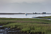A boat passes through the intracoastal waterway heading north through the Cape Romain National Wildlife Refuge near Charleston, South Carolina. The 66,287 acre National Wildlife Refuge encompass water impoundments, creeks, bays, emergent salt marsh and barrier islands most of which is only accessible by boat.