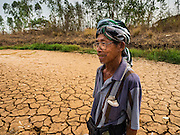 02 APRIL 2016 - NA SAK, LAMPANG, THAILAND:  A 79 year old farmer walks through the water tank the farmer built for his water buffalo in Sobjant village. He said this is the first time the tank has been empty, and that in 2015, also a year of drought, he still had 1.5 meters of water in his tank at this time of year. The village of Sobjant in Na Sak district in Lampang province was submerged when the Mae Chang Reservoir was created in the 1980s. The village was relocated to higher ground a few kilometers from its original site.    PHOTO BY JACK KURTZ