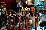 A barmaid pours a beer in Macche bar, Trastevere, Rome, Italy.