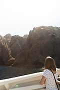 Woman looking at view on jet boat on sea, Scandola Nature Reserve, Corsica, France