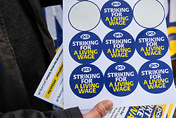 London, UK. 13th February, 2019. A Public & Commercial Services (PCS) union member hands out stickers on a picket line outside the Department of Business, Energy and Industrial Strategy (BEIS) after outsourced worker colleagues walked out for their second day of strike action to demand the London Living Wage and an end to outsourcing. Union members handed out strike-themed cakes to supporters in return for donations to the strike fund.