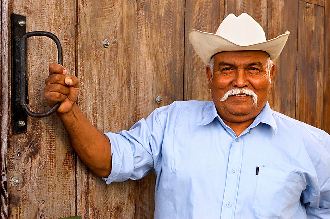 Smiling Cattle Rancher Poses In Front Of A Horse Barn In The Guanacaste, Costa Rica.