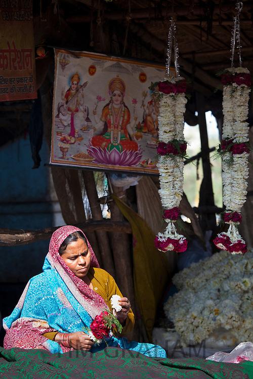 Indian woman at work stringing garlands at Mehrauli Flower Market, New Delhi, India