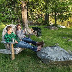 A young couple enjoy an evening in a giant Adirondack chair at the Appalachian Mountain Club's Gorman Chairback Lodge. Near Greenville, Maine.