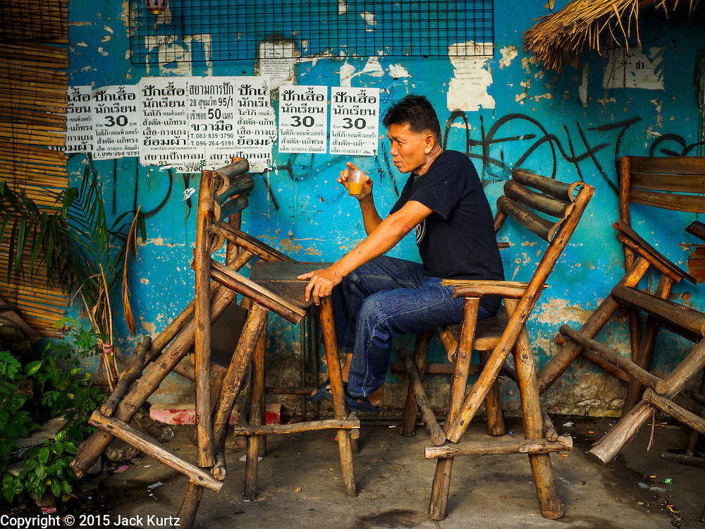 02 SEPTEMBER 2015 - BANGKOK, THAILAND: A man drinks a cup of coffee in street side coffee stand in the Bang Chak Market. The Bang Chak Market serves the community around Sois 91-97 on Sukhumvit Road in the Bangkok suburbs. About half of the market has been torn down, vendors in the remaining part of the market said they expect to be evicted by the end of the year. The old market, and many of the small working class shophouses and apartments near the market are being being torn down. People who live in the area said condominiums are being built on the land.         PHOTO BY JACK KURTZ