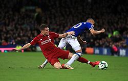 Liverpool's James Milner (left) tackles Everton's Richarlison during the Premier League match at Goodison Park, Liverpool.