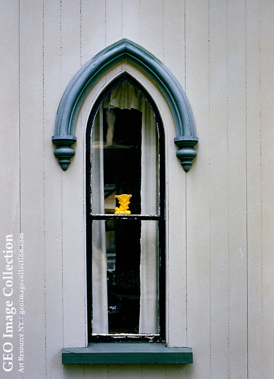 A blue Gothic arch decorates the exterior of a narrow arched window.