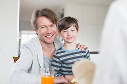 Portrait of father and son at breakfast table, smiling