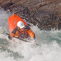 Play boat kayaker Jeff Germaine (MR) wave surfing on Kananaskis River, Kananskis Provincial Park, near Banff and Calgary, Alberta, Canada
