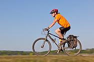 Panned shot of cyclist riding along the Carsington Reservoir Dam wall, Derbyshire
