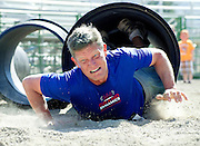 PRICE CHAMBERS / NEWS&GUIDE<br /> Marshall White, 39, emerges from a dark, gravel-filled tube while running in the obstacle-laden Tough Towner race on Sunday. Hundreds turned out for the event, this one dedicated to Jared Spackman.