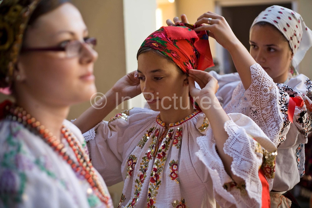 Girls help each other to tie a costume backstage during a folk event in Pecs, Hungary.Pecs has been chosen as the 2010 European City of Culture. The city is on the southern slopes of the Mecsek Hills and has a sub-Mediterranean climate. Settled by Romans as Sopianae, it was a significant Christian settlement. Later conquered by the Ottomans, it has important Turkish architecture.