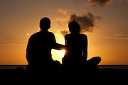 Couple sitting on a wall by the ocean and silhouetted against the sunset