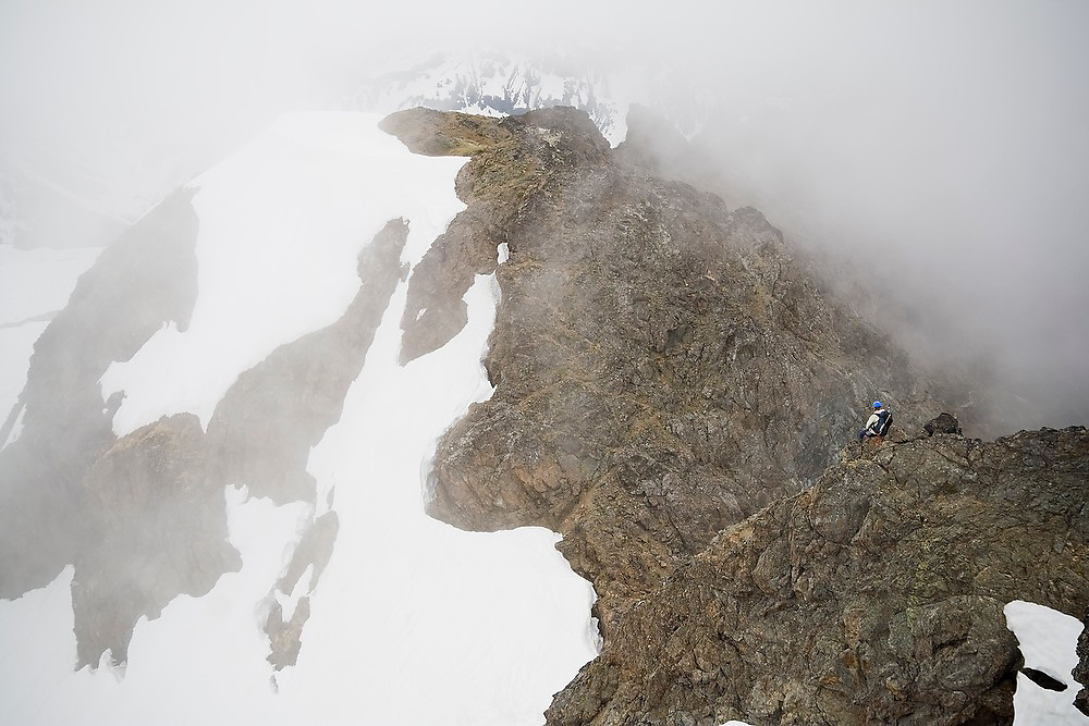 Valerie Wall sits and watches the clouds roll by from a ridge below the summit of Tomyhoi Peak, Mount Baker Wilderness, Washington.