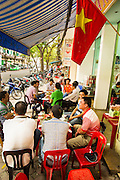 "09 APRIL 2012 - HANOI, VIETNAM:  People eat and drink at street side noodle stands in Hanoi, the capital of Vietnam. Street food has a long tradition in Vietnam. Beer, called ""bia"" in Vietnamese, is also frequently drunk at street side stands. Hanoi, established in 1010 AD, is one of the oldest permanent cities in Southeast Asia. PHOTO BY JACK KURTZ"