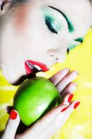 beautiful caucasian woman portrait eat an apple studio on yellow background
