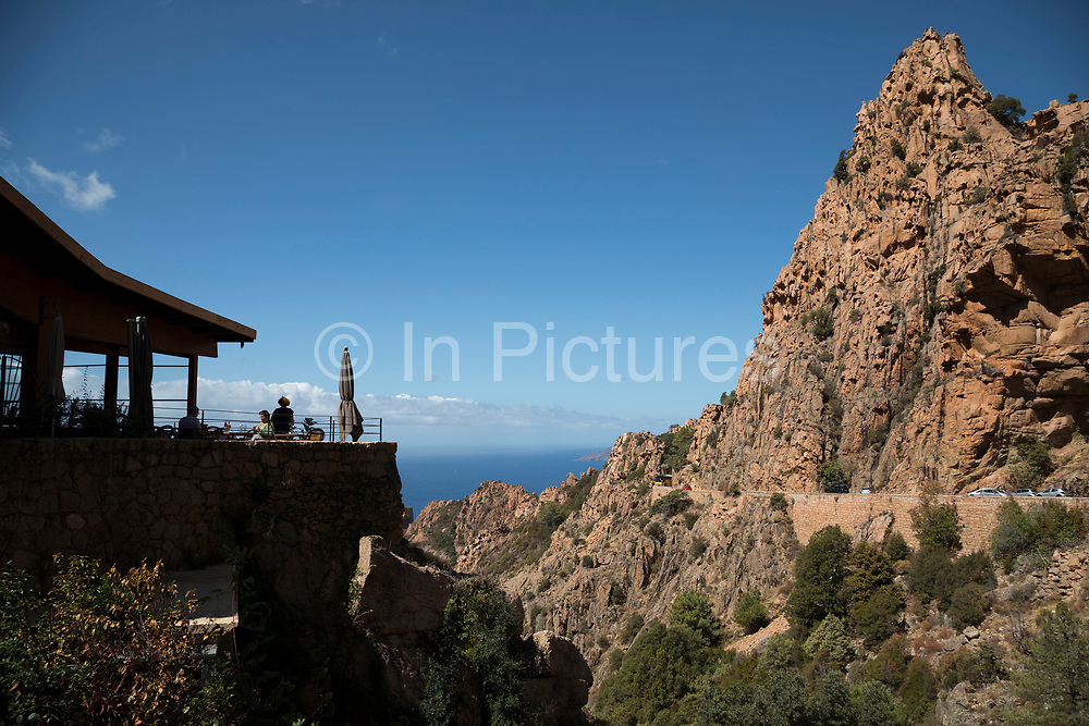 Mountain landscape of a cafe in the Calanques de Piana, gold and pink coloured granite rock formations formed by wind and rain erosion creating dramatic cavities as they descend into the sea at the gulf of Porto on 11th September 2017 in Piana, Corsica, France. Corsica is an island in the Mediterranean and one of the 18 regions of France. It is located southeast of the French mainland and west of the Italian Peninsula.