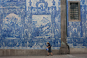 Elderly lady walks with sticks along the Rua de Fernandes Tomas with Azulejo tiles on the exterior of Capela Das Almas, on 20th July, in Porto, Portugal. The Churchs magnificent panels depict scenes from the lives of various saints, including the death of St Francis and the martyrdom of St Catherine. Eduardo Leite painted the tiles in a classic 18th-century style, though they actually date back only to the early 20th century.