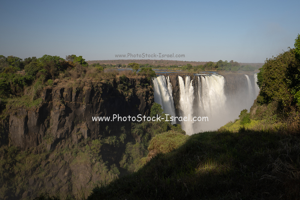 Victoria Falls, Named by David Livingstone in 1855 after Queen Victoria, The waterfall is formed by the Zambezi River falling into a 100 metre deep chasm running east to west across the flow of the river. The river is on the Zimbabwe-Zambia border.