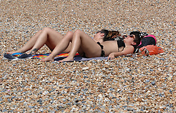 © Licensed to London News Pictures. 13/06/2014. Brighton, UK. Woman sunbathing on Brighton beach. Today, Friday 13th June is expected to be the hottest day of the year so far with temperatures hitting nearly 30C at some locations. Brighton beach is slowly filling up with sunbathers and people wanting to relax by the beach. Photo credit : Hugo Michiels/LNP