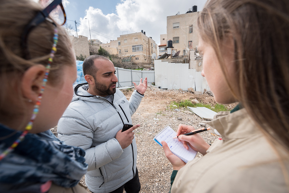 29 February 2020, Jerusalem: 26-year-old Mohammad Bashiti shows his home in the Shu'fat village in Jerusalem to participants Kristin (right) and Charlotte (left) in the Ecumenical Accompaniment Programme in Palestine and Israel (EAPPI), where he has just had a part demolished. As building permits are notoriously difficult, in some cases impossible, for Palestinians to obtain, demolition of houses stated not to have the relevant permits is common in the area. This time, the family lost their living room, two bathrooms, and kitchen.