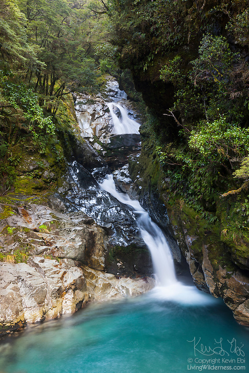 Falls Creek drops from the mountains in Fiordland National Park, New Zealand, forming several small waterfalls. Fiorland is New Zealand's largest national park and is located in the southwestern portion of the South Island.