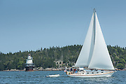 Fox Island Thorofare, ME - 11 August 2014. The sloop Loon passing Goose Rocks light. The light is ownd by Beacon Preservation, and is an active aid to navigation.