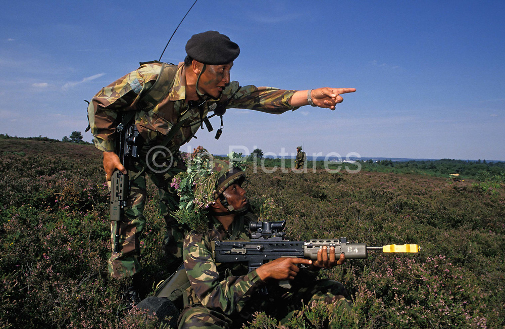 An instructor with the Royal Gurkha Rifles points a recruit towards an objective while on tactical training manoeuvres on heathland above Farnborough, on 5th August 1996, in Farnborough, England. Nepali-born boys belong to an elite Regiment of the British army. Every year 60,000 boys attend recruiting sessions in villages and towns in the Himalayan Kingdom but only 150 are selected each year to serve on active duty across the world. They fly to the UK for basic soldier training where they learn the skills required for infantry, transport, communications or clerical duties. Their reputation as a fierce but intensely loyal fighting force and many Victoria Crosses were won for bravery during World War 2. Here they are seen cradling modern SA-80 rifles while dressed in camouflaged helmets with oak leaves.