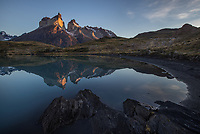 Hones of Paine sunrise reflects in the calm waters of Lago Nordenerskjold, Torres del Paine National Park, Chile