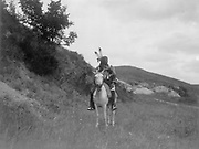 Sioux Indian on horseback, wearing two feathers, beaded buckskin shirt, and leggings, hills in background, c1907. Photograph by Edward Curtis (1868-1952).