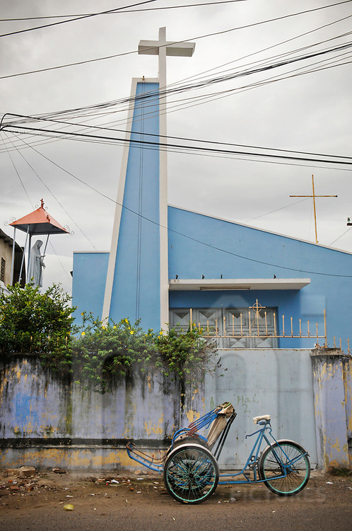 Architecture of a modern church with a rickshaw parked in front of the gate. Nha Trang, Vietnam, Southeast Asia