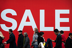 © Licensed to London News Pictures.17/12/2013. London, UK. Pedestrians walk past a sale sign on Oxford Street only a week before Christmas.Photo credit : Peter Kollanyi/LNP