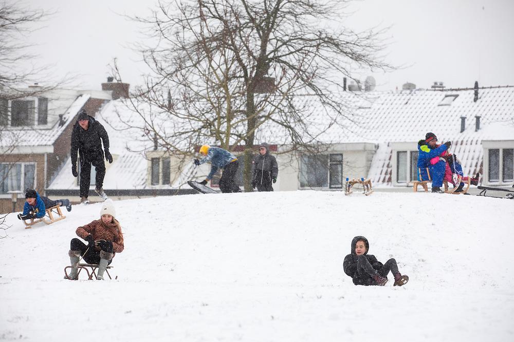 In Utrecht glijden mensen van een heuvel. Nederland geniet van de eerste sneeuw sinds lange tijd.<br /> <br /> In Utrecht people sled from a hill. People in the Netherlands enjoy the first snow since years.
