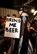 """Glastonbury Festival, 2015. Shangri La is a festival of contemporary performing arts held each year within Glastonbury Festival. The theme for the 2015 Shangri La was Protest.  Backstage on the Hell stage, man in costume holds """"Bring me a Beer"""" sign."""