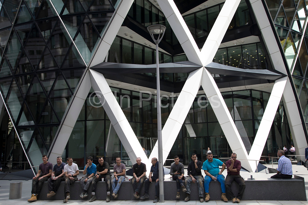 Line of workment taking a break sitting on a bench outside the Gherkin in the City of London, England, United Kingdom. Exterior of the Gherkin at 1 St Mary Axe. This iconic building is one of the best loved buildings in London with its distinctive bullet like shape and twisted glass structure.