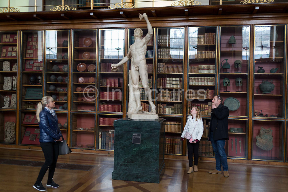 Visitors admire the sculpture of Rondaninis Faun - a 2nd century Roman copy of a Greek original - in the Enlightenment Gallery of the British Museum, on 11th April 2018, in London, England.